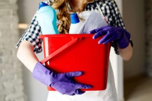 Nærbilde av kvinne med en bøtte med rengjøringsmidler