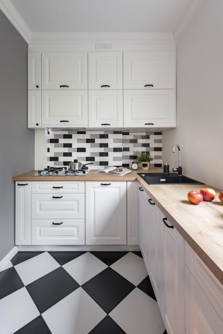 Lite kjøkken med hvit innredning og sjakk-fliser