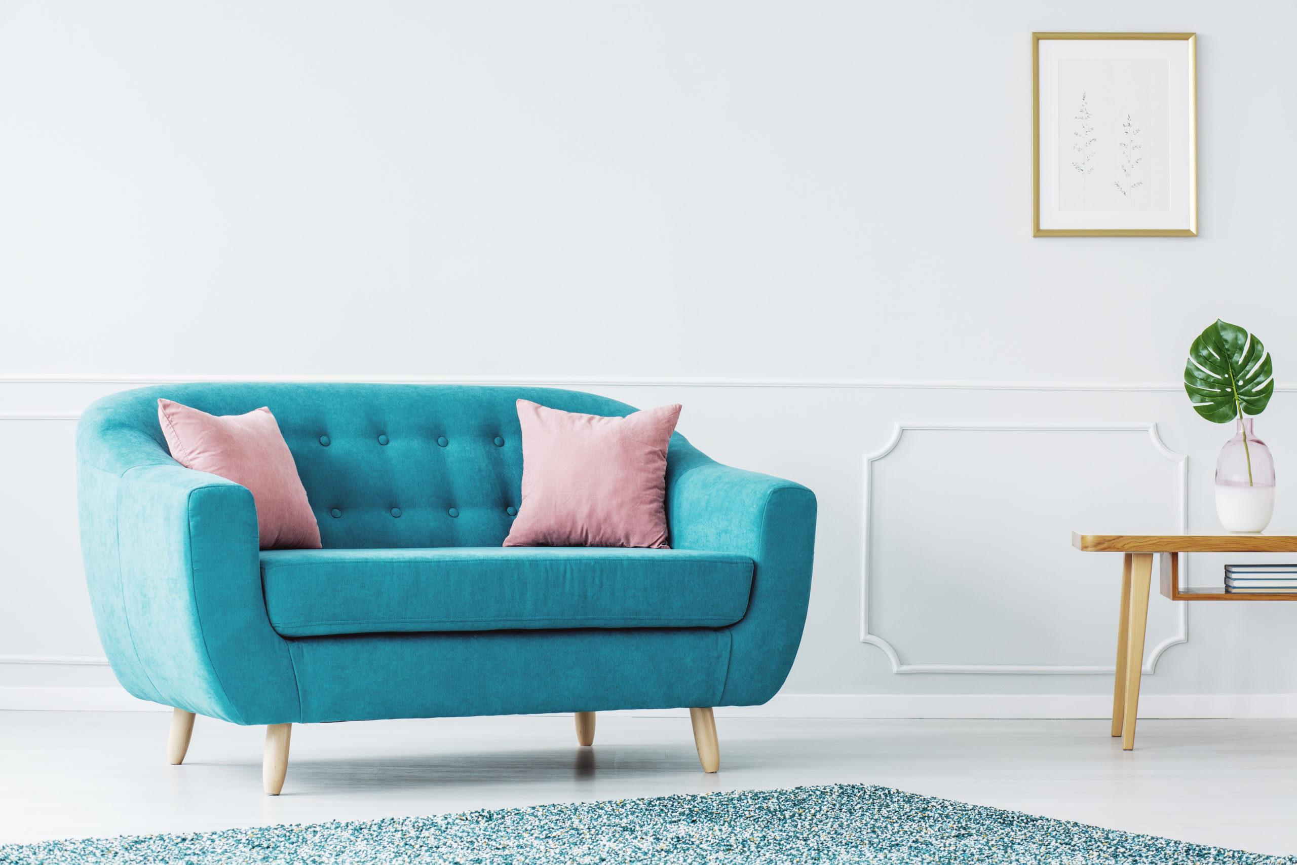 Turkis sofa i en minimalistisk stue